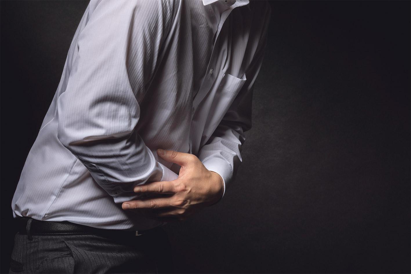 Person hält sich verkrampft den Bauch vor Schmerzen. Thema: Darmkrebs erkennen