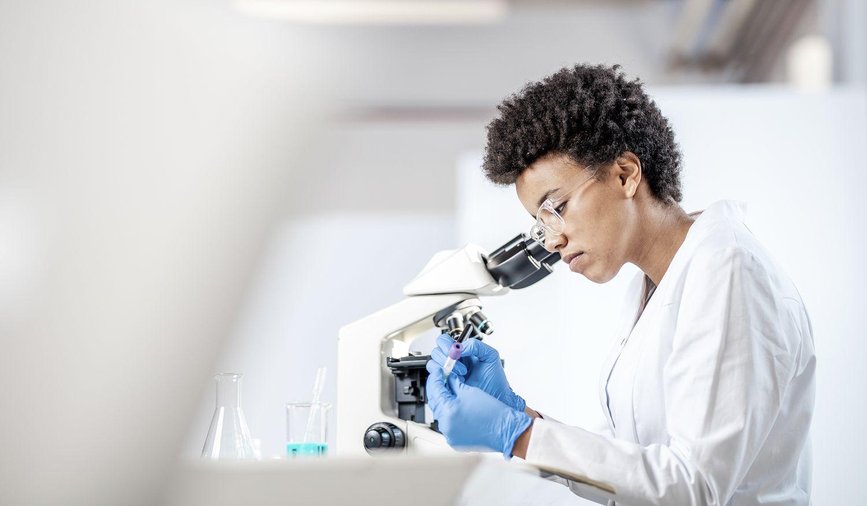 Eine Wissenschaftlerin arbeitet an einem Mikroskop.