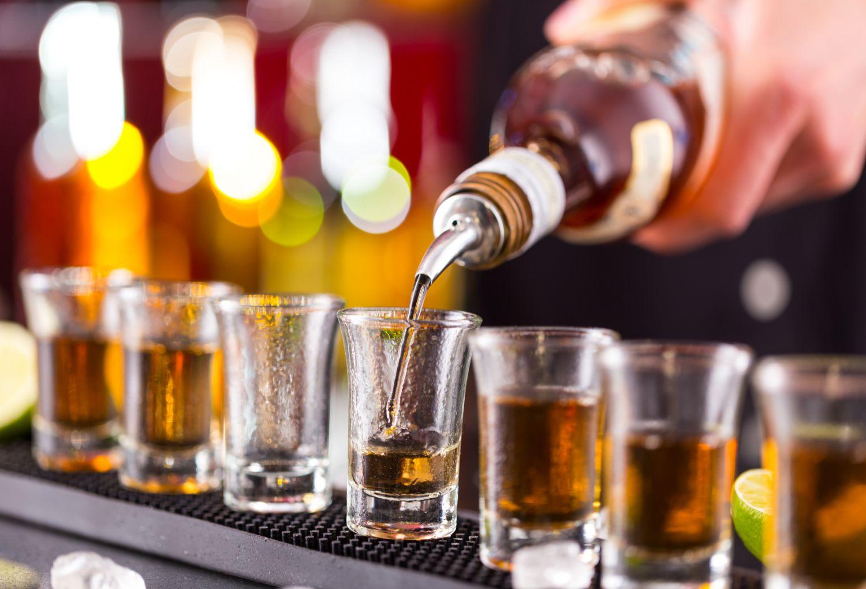 Hochprozentiger Alkohol wird in Schnapsgläser gegossen. Alkoholismus ist oft Ursache für das Hepatozelluläre Karzinom