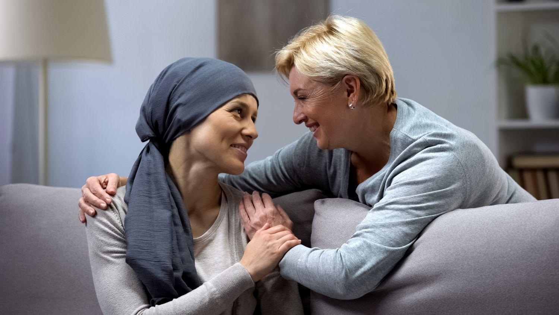 Mutter umarmt ihre Tochter, die Krebs hat