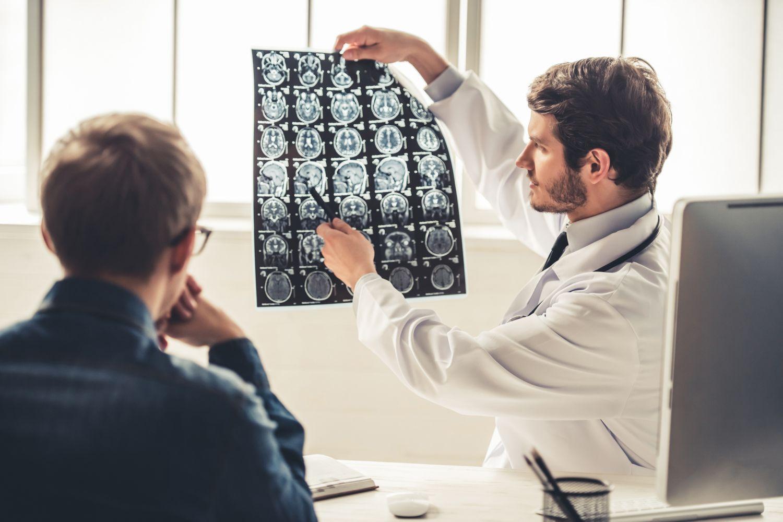 Ein Arzt bespricht mit einem Patienten eine Aufnahme des Hirns. Die Diagnose bösartiger Gehirntumor fällt dabei eher selten