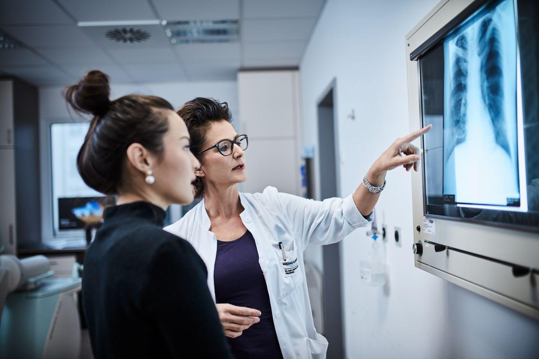 Ärztin zeigt Patientin ihr Röntgenbild.