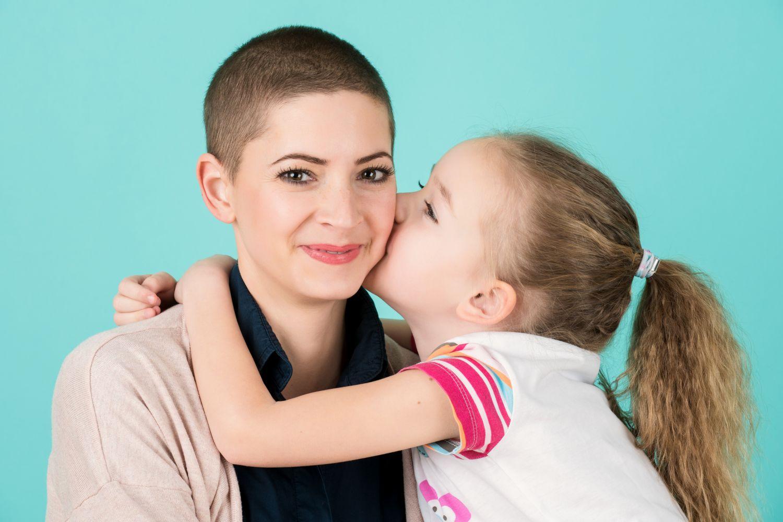 Fröhliche Mutter wird von ihrer kleinen Tochter umarmt und geküsst.